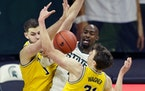 Michigan State guard Joshua Langford passed between Michigan center Hunter Dickinson (1) and guard Franz Wagner during the second half Sunday.