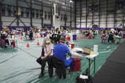 A woman waited to be vaccinated Friday at the Vikings Training Center in Eagan, which has been converted into a site administering the newly available