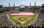 FILE - In this July 4, 2019, file photo, an American Flag is unfurled in the outfield during the playing of the National Anthem before the start a bas