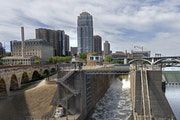 Water flowing over the St. Anthony Falls Dam (right) was slowed to a trickle and diverted around and through the old lock system (center)Tuesday morni