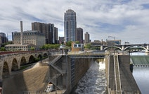 Water flowing over the St. Anthony Falls Dam, at right, was slowed to a trickle and diverted around and through the old lock system at center on Aug 1