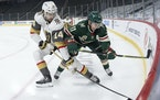 Nicolas Hague (14) of the Las Vegas Golden Knights and Zach Parise (11) of the Minnesota Wild fought for the puck in the first period.