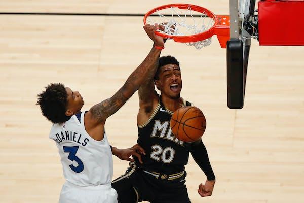 Atlanta Hawks forward John Collins (20) dunks against Minnesota Timberwolves forward Jaden McDaniels (3) in the second half of an NBA basketball game