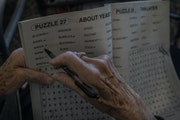Rosie Eberhard, a Oak Meadows Senior Home resident, filled out puzzles as she and other ladies sat near the entrance of the Oakdale senior home in Feb