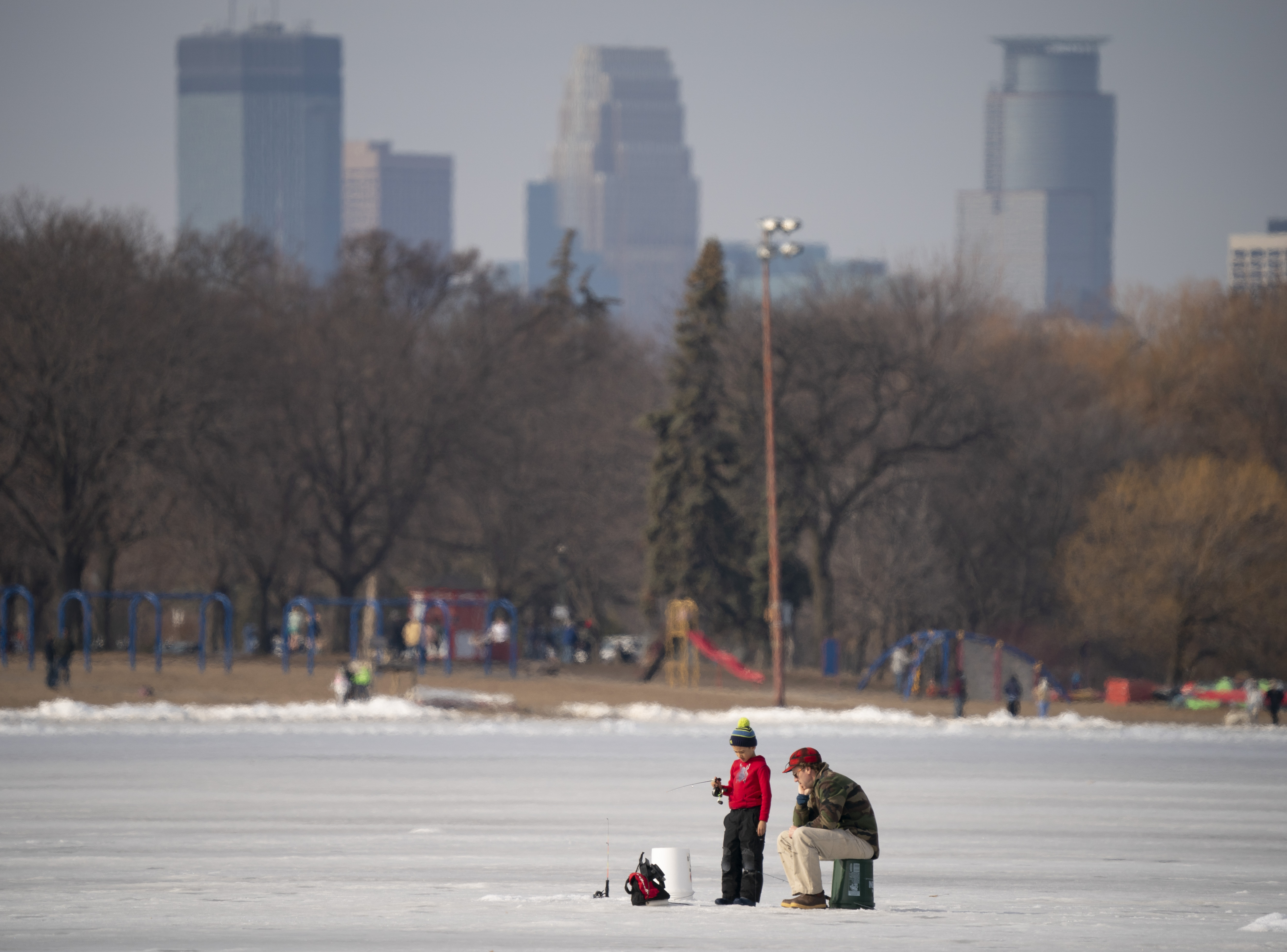 Andrew Johnson and his son, James, 6, fished while they still could at Lake Nokomis on Sunday afternoon as temperatures reached the high 50s.