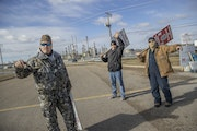 Members of Teamsters 120, from left, crane operator, Jim O'keefe, Scott Schulte, and Cheng Xiong, picketed outside the Marathon Refinery, Thursday,