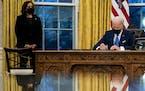 President Joe Biden signs executive orders as Vice President Kamala Harris looks on in February.