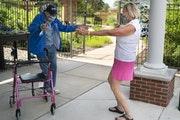 Victoria Conrad opened her arms to do a distant hug with her 99-year old father Howard Seitzer as they met for their first face-to-face visit since th