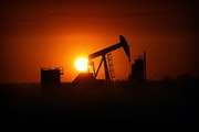 The sun set over the Bakken Oil Formation, behind an oil well near Williston, N.D., in 2013.