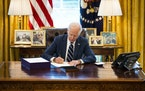President Joe Biden signs the American Rescue Plan in the Oval Office in Washington on Thursday. Even before the plan's passage, this year's defic