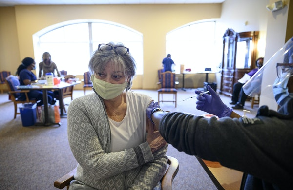 North Memorial nurse Maureen Kurgat vaccinated Catherine Rivard, 68, against COVID-19 in the lobby of her Minneapolis apartment building on Wednesday.