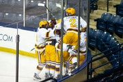Gophers players swarmed Sammy Walker in the corner after the team captain scored in overtime to beat Michigan 4-3 on Monday night in South Bend, Ind.