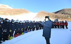 Chinese President Xi Jinping speaks with athletes and coaches at the National Alpine Skiing Center in Yanqing on the outskirts of Beijing during a tou