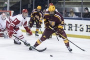 Gophers forward Blake McLaughlin controlled the puck as Wisconsin's Tyler Inamoto (5) defended during the championship game of the Big Ten men's h