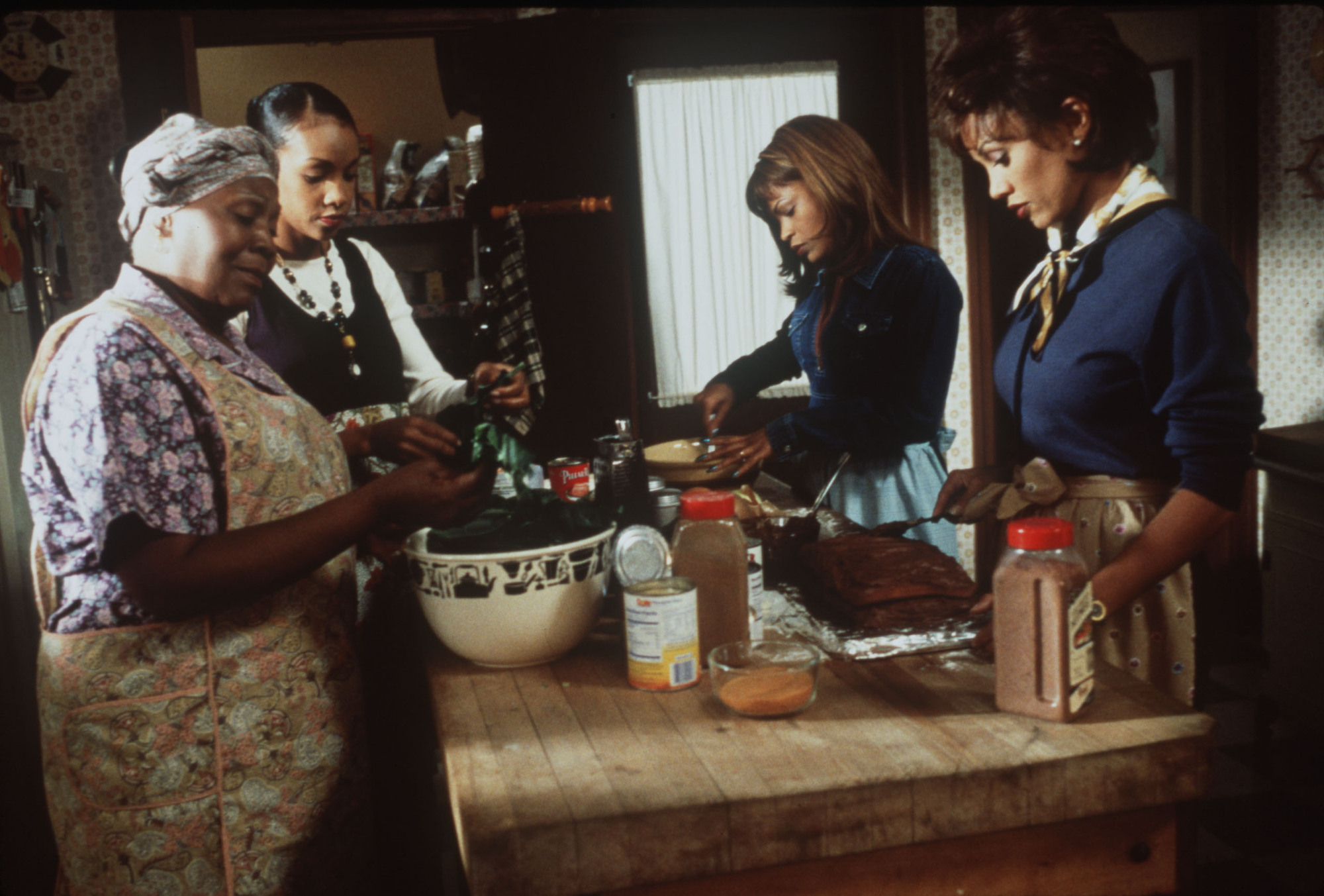 Irma P. Hall, left, as the family matriarch helps her daughters played by Vivacia A. Fox, Nia Long and Vanessa L. Williams, prepare for the weekly family dinner in 'Soul Food.'