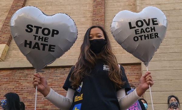 """Earlier this month, Chinese-Japanese American student Kara Chu, 18, holds a pair of heart balloons decorated by herself for the rally """"Love Our Comm"""