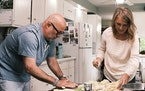 "Andrew Zimmern helps Helen Arends of Willmar, Minn., prepare a meal during the filming of ""Family Dinner."""