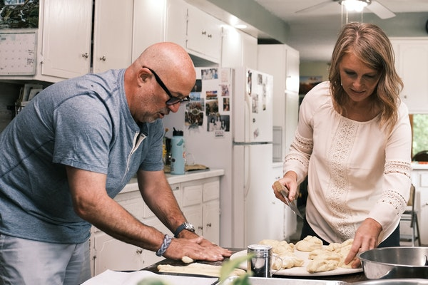 """Andrew Zimmern helps Helen Arends of Willmar, Minn., prepare a meal during the filming of """"Family Dinner."""""""