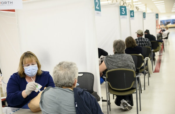 Blue Cross and Blue Shield of Minnesota nurse Debra Kloyda administered a dose of the Moderna COVID-19 vaccine to an elderly woman at North Memorial H