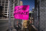 A sign was attached to a fence outside the Hennepin County Government Center.
