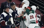 Wild defenseman Matt Dumba, center, is helped off the ice by Jonas Brodin, front, and Jordan Greenway after being injured in the second period