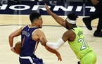 Timberwolves guard Josh Okogie, right, defends Phoenix guard Devin Booker during the second half of the Wolves' 123-119 win Thursday. (AP Photo/Rick