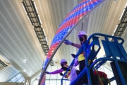 """Jen Lewin (right) helped install lights on """"The Aurora,"""" her new public artwork at MSP Airport."""