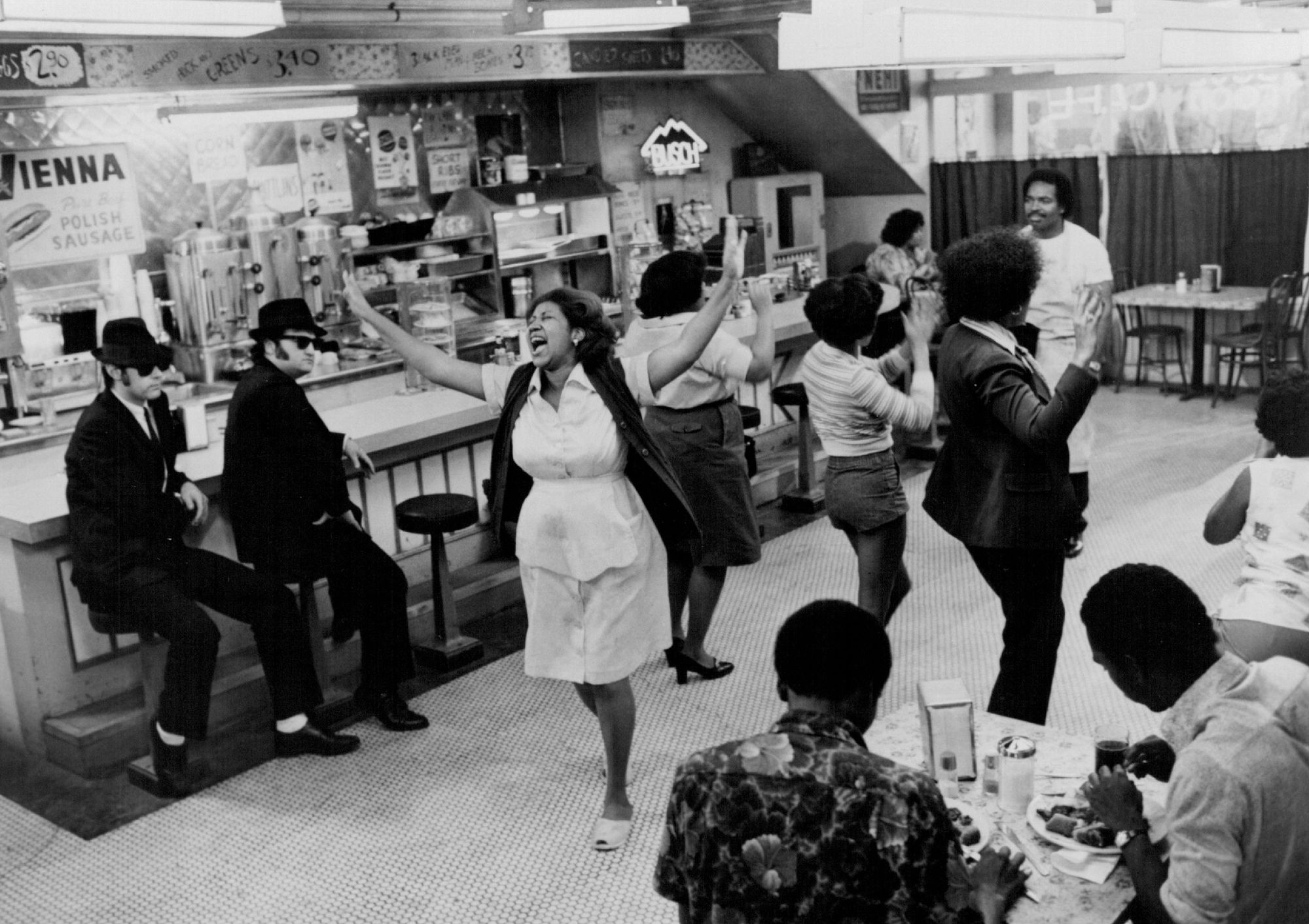 John Belushi, right, and Dan Aykroyd in 'The Blues Brothers' watch Aretha Franklin, as the owner of the Soul Food Cafe, sing 'Think!'