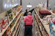 Volunteer Karen Purvis (back to camera) helps Sandy Tenwolde select items at Wabasha Area Food Share. (Photo by John Reinan?