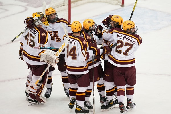 Gophers players mobbed Ryan Johnson after the defenseman scored his first career goal earlier this season.