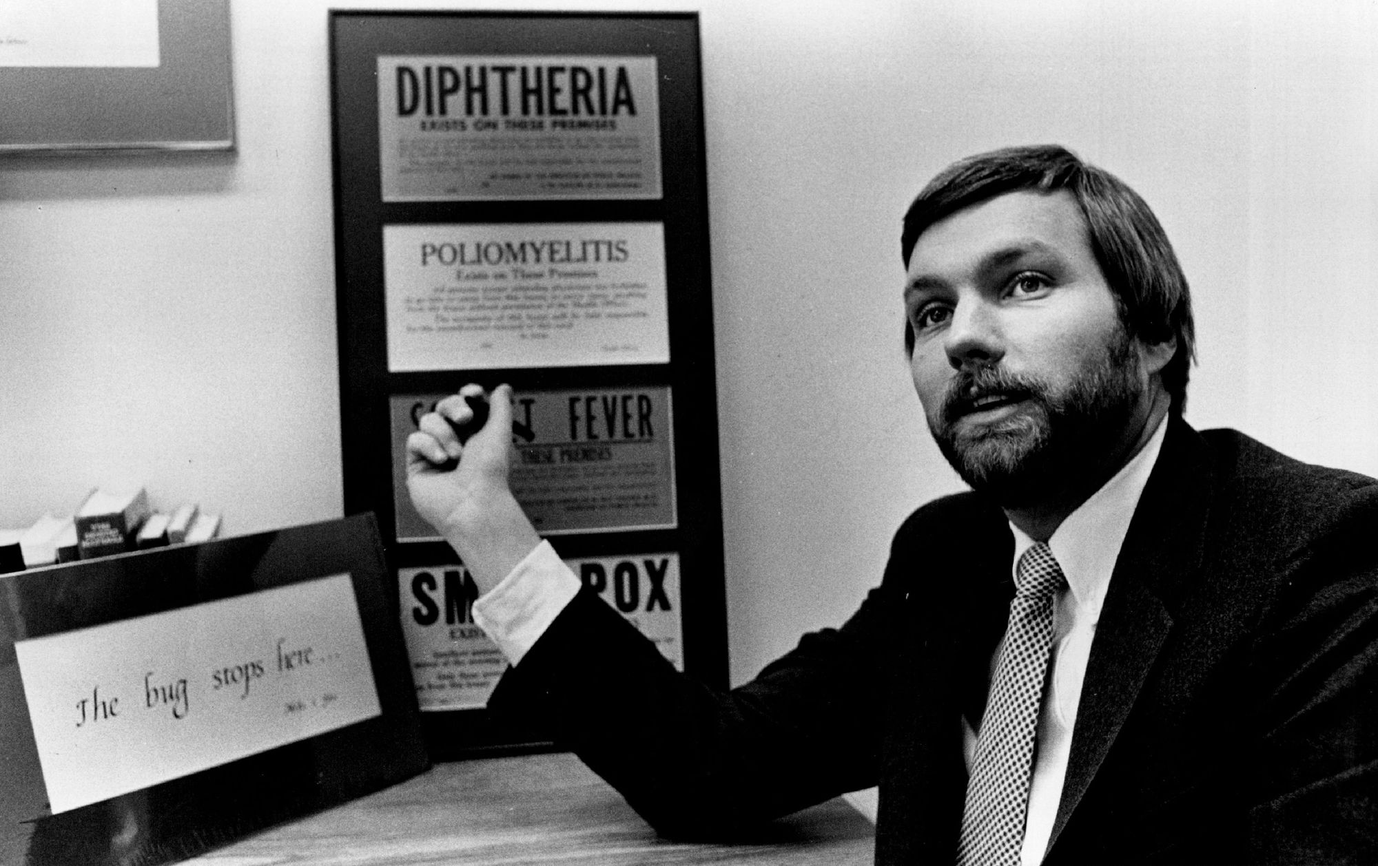 February 16, 1986 State Epidemiologist Michael Osterholm says quarantine of people carrying AIDS virus is not the answer; 1930s-era quarantine signs for other diseases are on his office wall. February 7, 1986