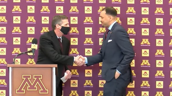 New men's basketball coach Ben Johnson shakes hands with Mark Coyle at Tuesday's press conference.