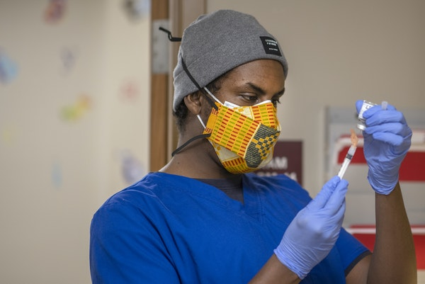 People's Center Clinic medical assistant Kayse Abdirahman prepped doses of the Moderna COVID-19 vaccines at the clinic.