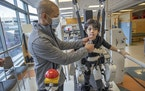 Tony Lee was by Navon's side as he took on the Lokomat machine during a physical therapy visit at Gillette Children's Specialty Healthcare on Feb.