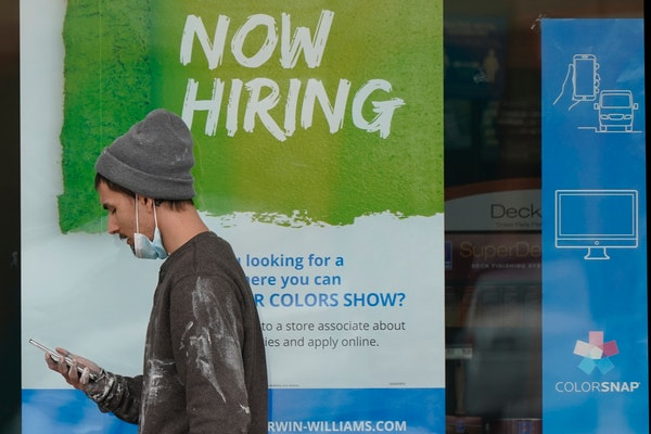 """A man walks past a """"Now Hiring"""" sign on a window at Sherwin Williams store, Friday, Feb. 26, 2021, in Woodmere Village, Ohio. Massive fraud in the"""