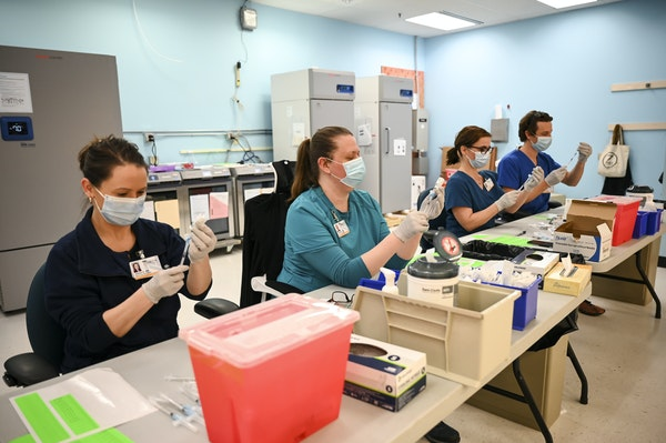 From left, Blue Cross and Blue Shield of Minnesota nurses Alison Stumne, Tamara Pierre, Jana Wagner and Kirk Randall filled syringes at a North Memori