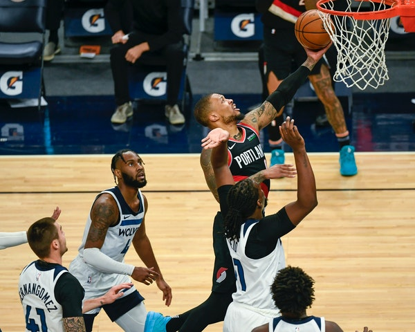Portland Trail Blazers guard Damian Lillard, top, drives past Minnesota Timberwolves center Naz Reid, right, forward Juancho Hernangomez (41) and guar