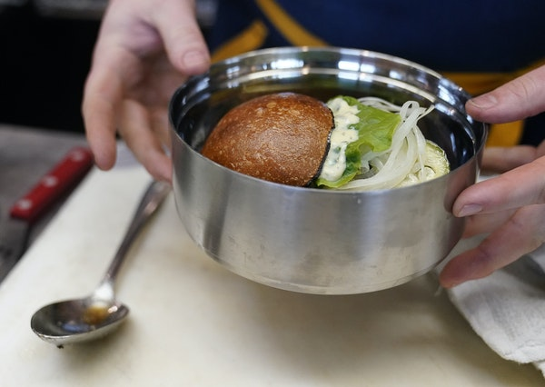 Dan Schmit, Wise Acre executive chef, prepares a Scottish Highland beef burger in a reusable stainless steel container.