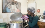 Chief coordinator Glenda Andrew checks the pot as she prepares West Indian meals with members of the Preston Windrush Covid Response team, at the Xave