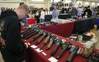 Gun enthusiasts view AR-15 semi-automatic assault rifle parts at a 2015 gun show in Del Mar, Calif.