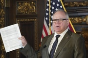 Gov. Tim Walz held up a supplemental budget at a news conference in 2020.