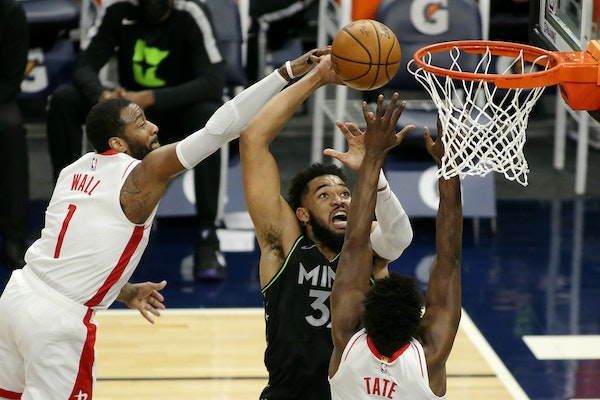 Minnesota Timberwolves center Karl-Anthony Towns (32) shoots against Houston Rockets guard John Wall (1) and forward Jae'Sean Tate (8) in the firs