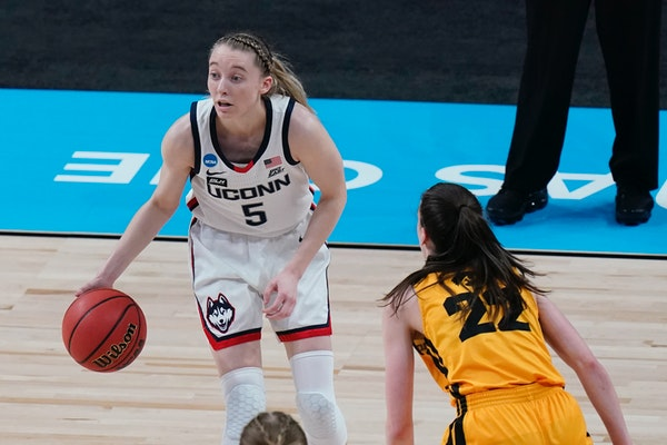 UConn guard Paige Bueckers (5) works the ball past Iowa guard Caitlin Clark (22) during the first half of a college basketball game in the Sweet Sixte