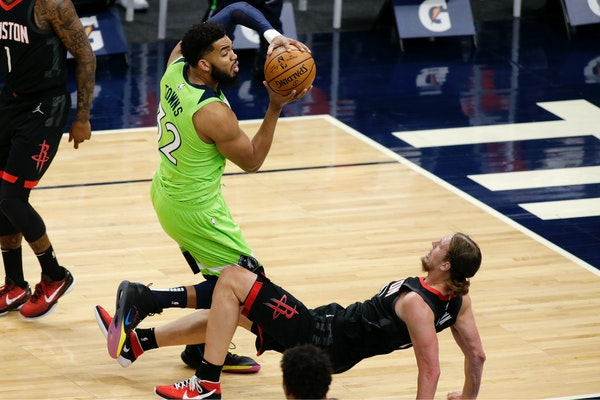 Rockets center Kelly Olynyk tried to take a charge but was called for a foul after a collision with the Wolves' Karl-Anthony Towns on Saturday nigh