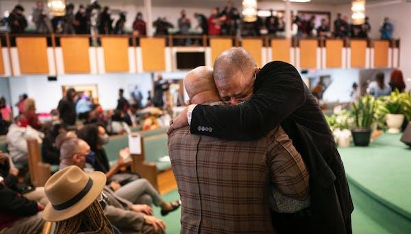 Rep. John Thompson, right, hugged the Rev. Jerry McAfee, pastor of New Salem Baptist Church, during a prayer service for George Floyd's family Sunda