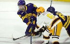 Minnesota State's Cade Borchardt, left, and Nathan Smith battled with the Gophers Mike Koster for the puck during the West Regional final.