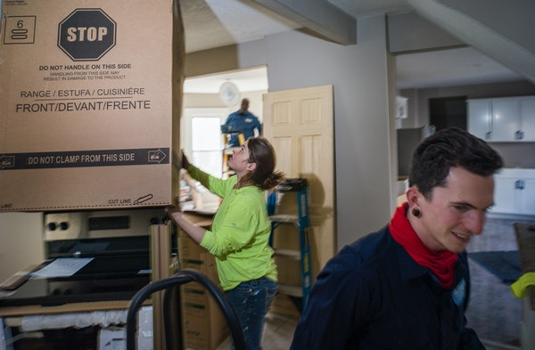 Subcontractor Sarah Stephenson installed appliances while master electrician McKeith Pearson and apprentice Noah Cappotto, right, put in lights for Fi