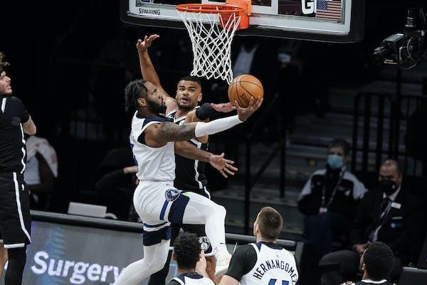 Minnesota Timberwolves' Jaylen Nowell, left, shoots over Brooklyn Nets' Timothe Luwawu-Cabarrot during the first half of an NBA basketball gam