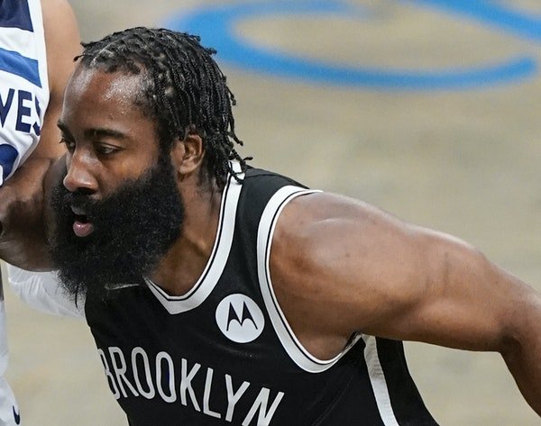 Brooklyn Nets' James Harden, right, protects the ball from Minnesota Timberwolves' Karl-Anthony Towns, left, during the first half of an NBA baske