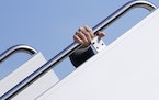 President Joe Biden holds onto the hand rail as he stumbles while boarding Air Force One at Andrews Air Force Base, Md., on March 19.